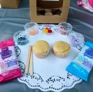 baked cupcakes and decorating materials